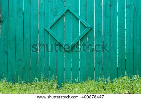 Green wooden fence with green grass - stock photo