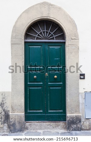 Green, wooden, Tuscan door in Italy (black and white) - stock photo