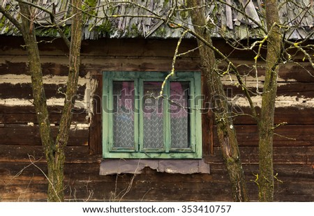 Green wooden window from a wooden house, framed by two trees - stock photo