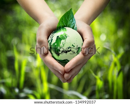 green world in the heart hand - grass background - stock photo