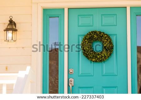 Green wreath decorating front door. - stock photo