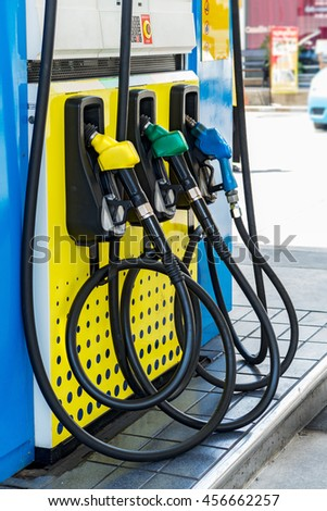 Green,Yellow and Blue fuel nozzles in the fuel dispenser in the Petrol Station - stock photo