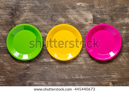 Green, yellow and pink color plates set  on wooden background - stock photo