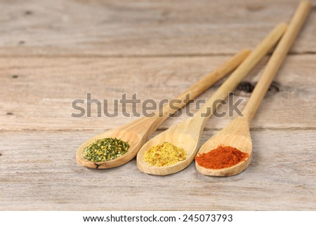 Green, yellow and red spice powder in long wooden spoons on rough country table - stock photo