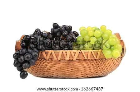 Greenand black grapes in basket. Isolated on a white backgropund. - stock photo