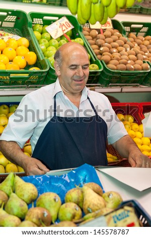 Greengrocer at the market stall - stock photo