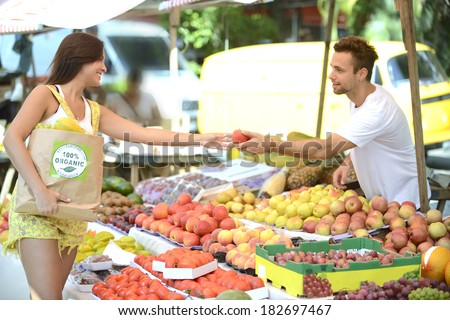 Greengrocer owner of a small business at an open street market, handing out a fruit to a consumer, carrying a shopping bag with 100% organic certified label. - stock photo