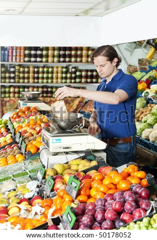 Greengrocer weighing fresh food on a digital scale - stock photo