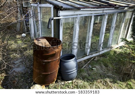 Greenhouse. The old and small hothouses standing in neglected garden ??, somewhere in poor part of Europe. - stock photo