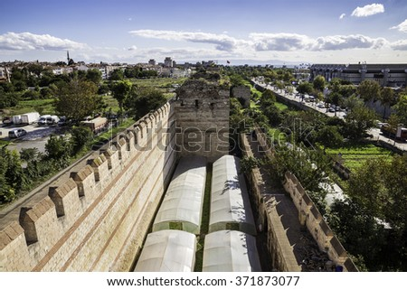Greenhouses and agricultural activities near Yedikule Fortress wall ruins and tower in Istanbul, Turkey - stock photo
