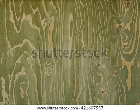 greenish wood panel with streaks created by knots and wavy shaped veins - stock photo