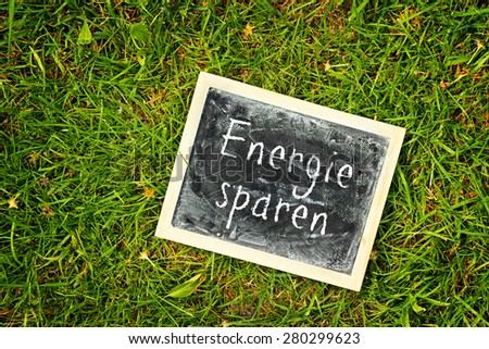 greeting card background for your text - blackboard - german for saving energy - stock photo
