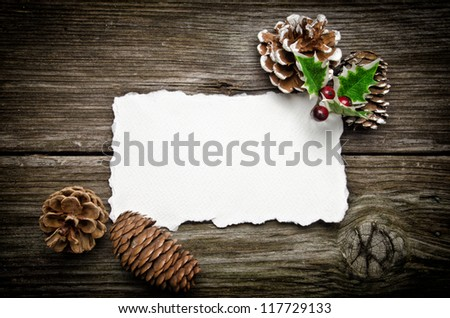 Greeting card for Christmas with pine cones and holly - stock photo
