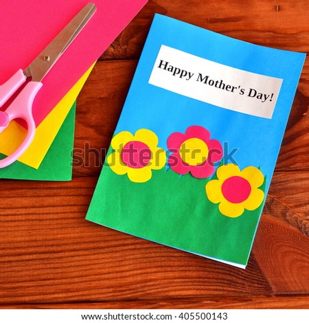 Greeting card Happy mother's day - easy children's crafts. Scissors, paper sheets on brown wooden background  - stock photo