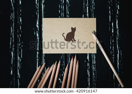 Greeting card with cat, kitten, pussy, tomcat, grapnel, letter, blank sheet for text and pencils lying on a dark wooden surface. Photography can be used for wedding invitations as the background. - stock photo