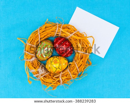greeting easter card with handmade easter eggs in nest in textile blue background - stock photo