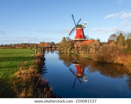 Greetsiel, Germany - December 6, 2014: Traditional Windmill working and still used to grind. The second mill is currently under renovation due to a violent hurricane. - stock photo