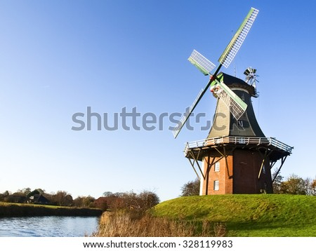 Greetsiel, Germany: Traditional Dutch windmills working and still used to grind. The green, western mill dates from 1856, the red, eastern mill was built in 1706. - stock photo
