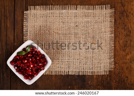 Grenadine seeds in white plate on canvas, wooden background, upper view - stock photo
