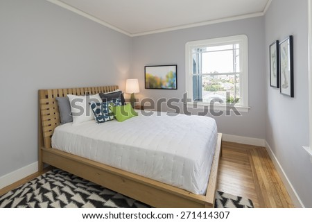 Grey bedroom with amazing wooden bed frame and decorated big expansive mattress with pillows in modern home. Copy space for art above the bed. - stock photo
