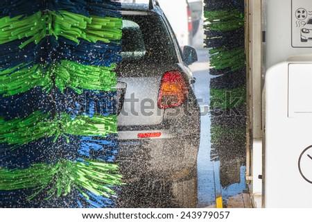 Grey car during washing process - stock photo