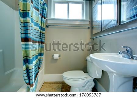 Grey color bathroom with brown tile floor, multi striped curtains - stock photo
