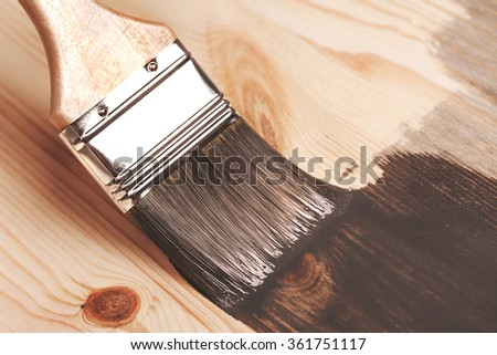 Grey color painting on wooden table or fence or wall, or flour, use for home decorated. House renovation. Half - painted surface. Smear of paint brush. Macro. - stock photo