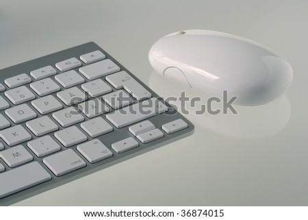 Grey computer keyboard with white keys and white wireless mouse on white reflective table top. - stock photo