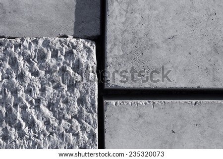 Grey concrete blocks surface with different texture. - stock photo