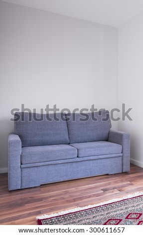 Grey couch on wooden floor in living room - stock photo