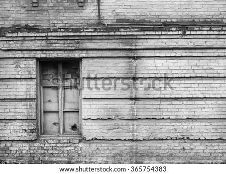 Grey damaged brick wall with broken door. Industrial background.  - stock photo