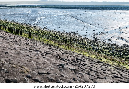 Grey, green and blue colored landscape with a dike of basalt stones and tar covered with algae and salt marshes that reflect the blue sky. - stock photo