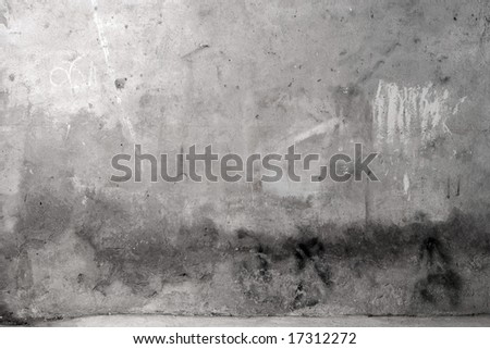 Grey grunge cement wall with some scribbles - stock photo