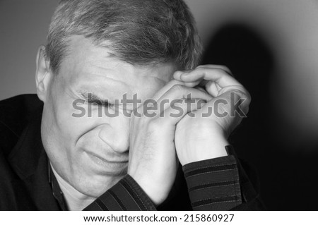 Grey-haired man in a suit at the age of forty-six years old hands covers one eye on the background of a rough wall with texture - stock photo
