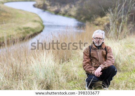 Grey Haired Older Man with Glasses and Brown Leather Jacket Sitting in a Nature Background - stock photo
