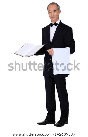 Grey haired waiter holding menu and table cloth - stock photo