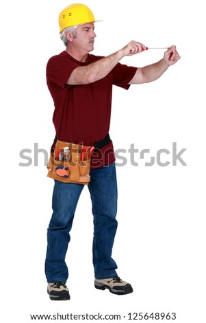 Grey-haired worker with screw-driver - stock photo