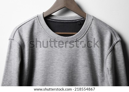 Grey jumper hanging on white wall - stock photo