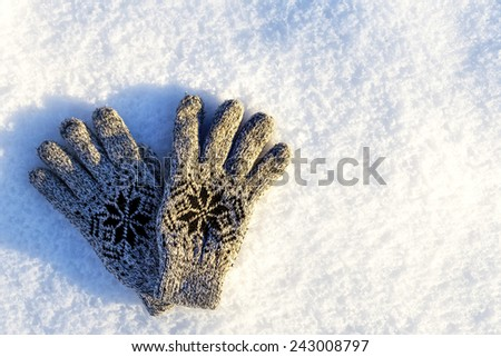 Grey knitted winter gloves on snow  - stock photo