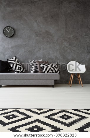 Grey living room with sofa, chair, pattern carpet and pillows in black and white  - stock photo