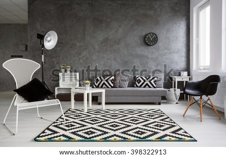 Grey living room with sofa, chairs, standing lamp, pattern carpet and trendy decorative details - stock photo