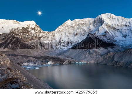 Grey moraine lake and snowy mountain peak in the moon light in Himalayas, Nepal. Mirror water of a big moraine lake. Imja Tsho moraine lake at the foot of the Imja Glacier. - stock photo
