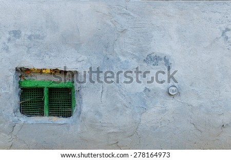 Grey old concrete wall with green window at the bottom left. Backgrounds, Wall, Textured, Gray, Stone Material - stock photo