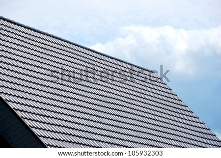grey roofing tile against the blue sky - stock photo