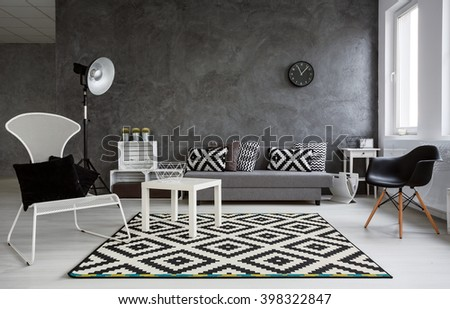 Grey room with sofa, comfortable chairs, standing lamp, small wood table and stylish pattern decorations in black and white - stock photo