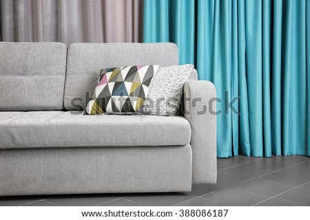 Grey sofa against blue curtains in the room - stock photo
