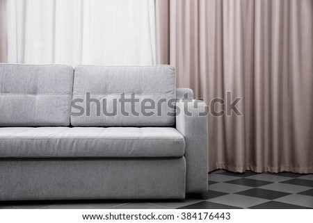 Grey sofa against curtains in the room - stock photo