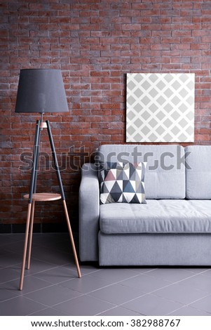 Grey sofa and floor lamp against brick wall in the room - stock photo
