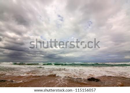 grey stormy clouded sky over green aqua ocean waves - stock photo