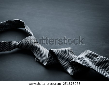 Grey tie on dark background - stock photo